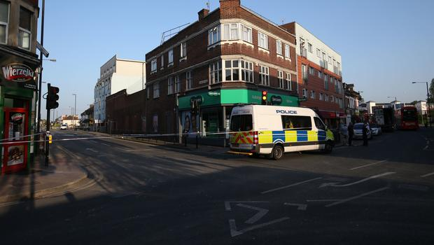 Police at the junction of Palmerston Road and the High Street, in Wealdstone after two boys were shot (Jonathan Brady/PA)