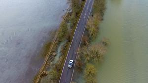 Cars drive along the A1101 in Welney, Norfolk, where the flooded road has finally cleared of water after two months submerged (Joe Giddens/ PA)
