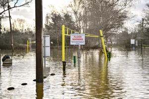 A flood warning sign at the entrance to a flooded car park beside Tewkesbury Abbey, where flood watches were in place (Ben Birchall/PA)