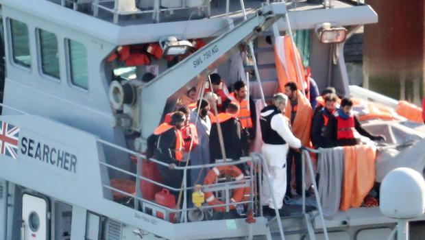 Migrants are brought ashore on an upper deck of a Border Force vessel in Dover (Gareth Fuller/PA)