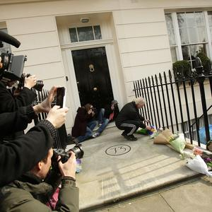 A man lays a bunch of flowers outside the home of Lady Margaret Thatcher in Belgravia, London following her death