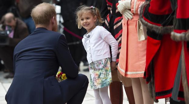 The Duke of Sussex is presented with a posey by four-year-old Zofia Zdenkowska (Geoff Pugh/The Daily Telegraph/PA)