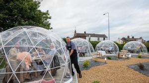 Owner and chef Josh Green checks on diners inside the outdoor dining pods which have been installed for social distancing at The Barn Restaurant, Terrington St John near Wisbech, Cambridgeshire (Joe Giddens/ PA)