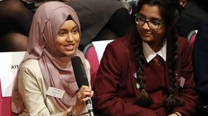 Ayesha Begum (left), 17, asks Michelle Obama a question as she appears via a video link at Mulberry School for Girls, London, as well as to other adolescent girls around the world