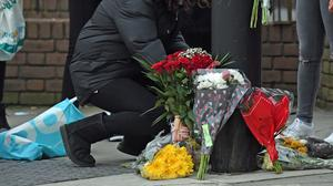 A woman lays a floral tribute on Ackmar Road near Parsons Green Tube station in London where Hani Soloman, 18, was fatally stabbed on Thursday evening. (Kirsty O'Connor/PA)