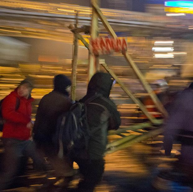 Anti-government protesters carry a catapult, used for hurling petrol bombs, at a barricade in central Kiev (AP)