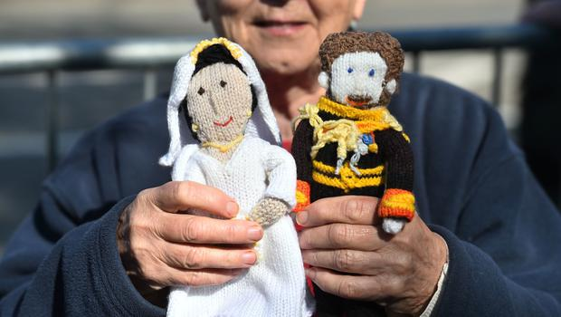 A royal fan holds knitted dolls of Prince Harry and Meghan Markle ahead of their wedding in St George's Chapel (Kirsty O'Connor/PA)
