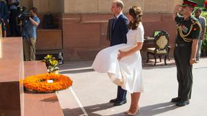 The Duchess of Cambridge struggles to control her dress in strong winds as the royals lay a wreath at the India Gate in New Delhi