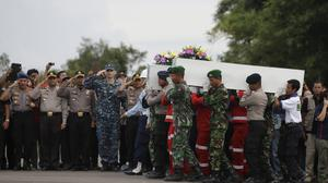 Members of the National Search And Rescue Agency and Indonesian soldier carry coffins containing bodies of the victims from irAsia Flight 8501 to transfer to Surabaya (AP Photo/Achmad Ibrahim)