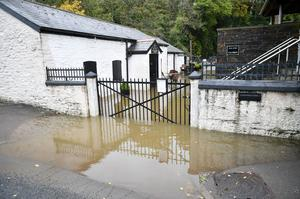 The Adberdulais tinworks and waterfall centre entrance is flooded in South Wales (Ben Birchall/PA)