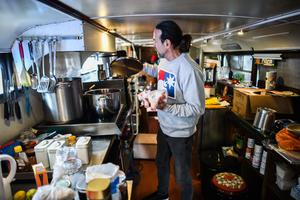 A man known as Johnny the Hungarian Chef prepares a meal for homeless people inside an old double-decker bus (Steve Parsons/PA)