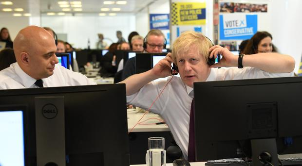 Chancellor Sajid Javid helps Mr Johnson work the phone system at Conservative Campaign HQ on Sunday morning (Stefan Rousseau/PA)