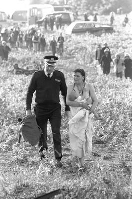 A woman holding a baby as she is led away by a policeman after violence erupted due to people attempting to hold a banned pop festival at Stonehenge in 1989 (PA)