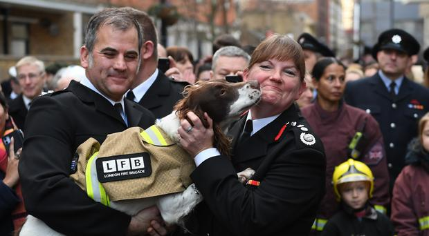 London Fire Brigade (LFB) Commissioner Dany Cotton (right) is greeted by a dog, as members of the London Fire Brigade line Union Street as a Guard of Honour, on her last day in office before stepping down from her role on New Year's Eve.