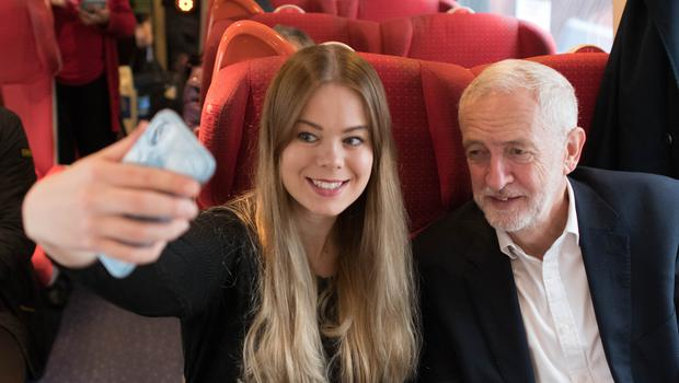 Labour Party leader Jeremy Corbyn meets a supporter on a train on his return from a visit to Sheffield (Stefan Rousseau/PA)
