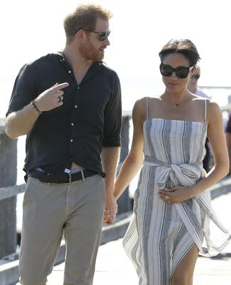 Meghan holds her hand on her bump as she and Harry walk along Kingfisher Bay Jetty on Fraser Island, Queensland (Kirsty Wigglesworth/PA)