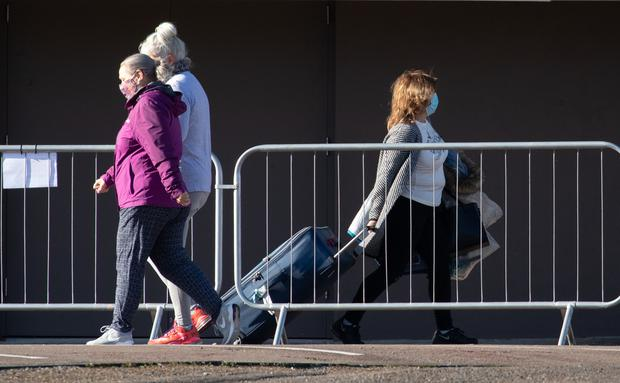 Guests take part in their daily exercise, left, as another, right, leaves the Radisson Blu Edwardian hotel near Heathrow Airport (Andrew Matthews/PA)