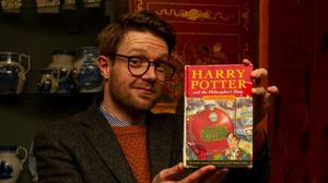 Jim Spencer, of Hansons' auctioneers, holding up the rare copy of Harry Potter and The Philosopher's Stone first edition hardback (Hansons/PA)