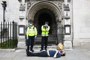 Police stand beside a laying protester during an Extinction Rebellion demonstration in central London (Stefan Rousseau/PA)