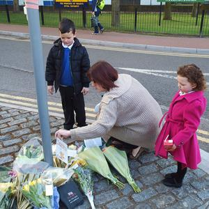 A woman and her two children lay a postcard on floral tributes outside The Royal Artillery Barracks in Woolwich