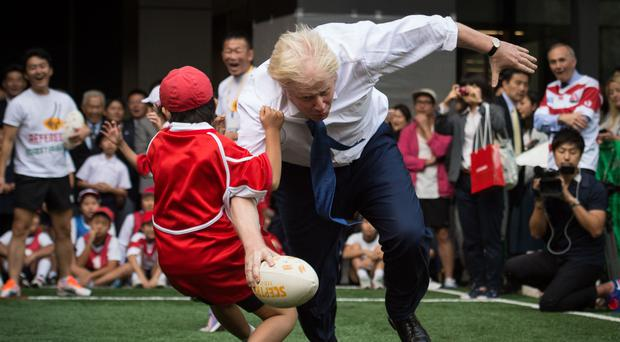 Boris Johnson knocked a schoolboy over during a game of rugby in Japan (Stefan Rousseau/PA)