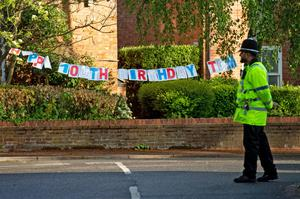 A policeman passes a Happy Birthday banner to mark the 100th birthday of Second World War veteran Captain Tom Moore close to his home in Marston Moretaine, near Bedford (Joe Giddens/PA)