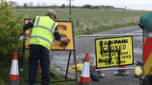 A worker removes a swastika spray-painted on the sign (Owen Humphreys/PA)