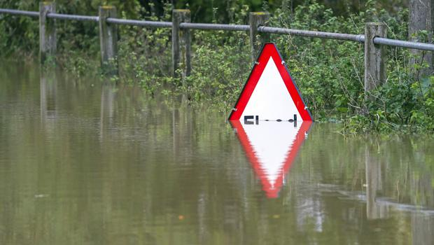 A half submerged sign warning drivers of a flooded road is flooded in Tewkesbury, Gloucestershire (PA)