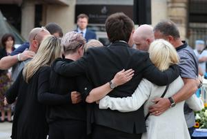 Family members of the three victims comfort each other (Steve Parsons/PA)