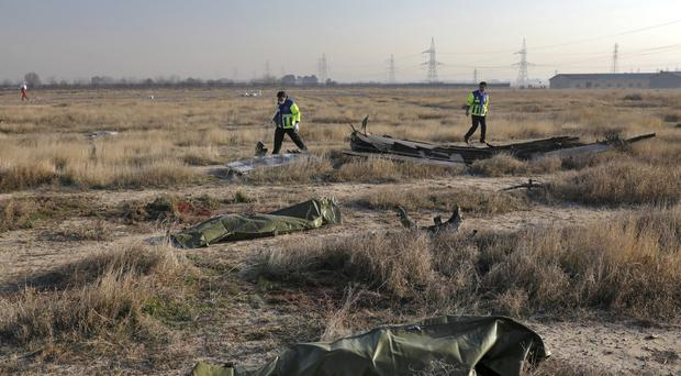 Rescue workers search the scene where a Ukrainian plane crashed (Ebrahim Noroozi/AP)