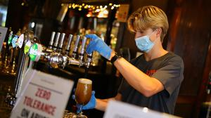 Bar staff in PPE pour drinks at the reopening of The Toll Gate (Aaron Chown/PA)