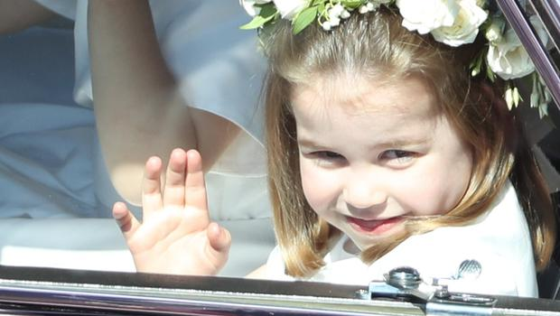 Princess Charlotte waves to the crowd as she travels to the wedding (Andrew Milligan/PA)