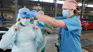 Medical staff put on their personal protective equipment (PPE) at an MOT testing centre in Belfast, Northern Ireland, which is being used as a drive through testing location for Covid-19, as the UK continues in lockdown to help curb the spread of the coronavirus.