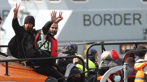 A group of people thought to be migrants wave as they are brought into Dover, Kent, on the RNLI Fraser Flyer Lifeboat following a small boat incident in the Channel (PA)