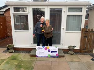 Diane Bate celebrates her Lotto win with husband Michael at their home in Rhyl (National Lottery/PA)