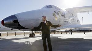 Sir Richard Branson poses with SpaceShipTwo at a Virgin Galactic hangar at Mojave Air and Space Port in Mojave (AP)