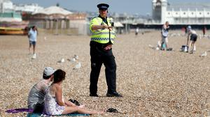A police officer advises people to leave the beach during the warm weather in Brighton (Gareth Fuller/PA)