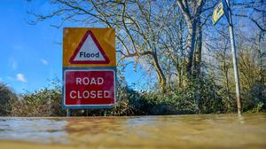 A road closed sign pokes out above floodwater and alerts motorists of flooding in Gloucestershire (Ben Birchall/PA)