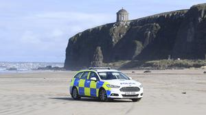 A police car patrols Downhill Beach, County Londonderry, under Mussenden Temple, as the UK continues in lockdown to help curb the spread of the coronavirus (Michael Cooper/PA)