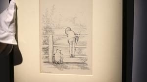 A drawing by EH Shepard of Winnie the Pooh, as the bear plays Poohsticks with Piglet and Christopher Robin