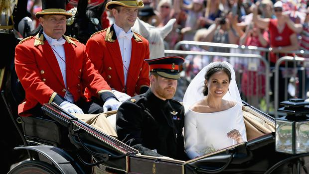The Duke and Duchess of Sussex ride in an open-topped carriage through Windsor Castle (Jeff J Mitchell/PA)