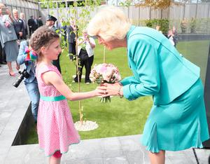 The Duchess of Cornwall is presented with a posy of flowers by seven year old Victoria Grieves during the opening of the memorial garden at the Police Service of Northern Ireland HQ in Belfast