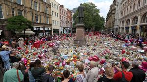 People look at flowers and tributes left in St Ann's Square in Manchester following the Manchester Arena terror attack as the brother of Manchester suicide bomber Salman Abedi has been released without charge( Danny Lawson/PA)