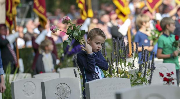 A child prepares to lay flowers on gravestones during a memorial service near Arnhem (Steve Parsons/PA)