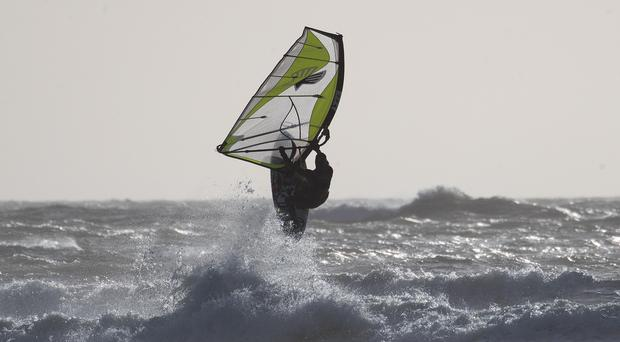 A windsurfer jumps in the air after hitting a wave in the sea off of West Wittering beach in West Sussex.