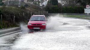 A motorist negotiates flood water in Starcross, Devon (PA)
