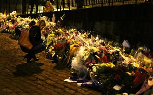 A woman lights a candle as she leaves flowers near the Clutha crash scene (Andrew Milligan/PA)