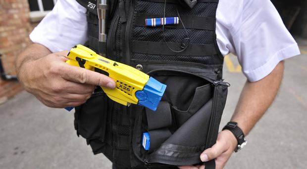 Police officer holstering a Taser X26 (Ben Birchall/PA)