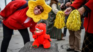 A woman wearing a daffodil on her head poses with a Welsh red dragon during a St David's Day Parade in Cardiff (Ben Birchall/PA)