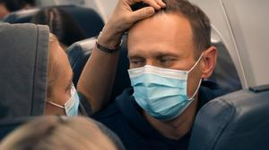 Alexei Navalny and his wife Yulia sit on the plane on a flight to Moscow (AP Photo/Mstyslav Chernov)